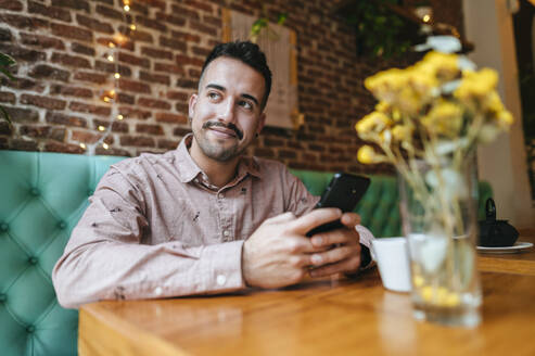 Smiling man in a cafe holding cell phone - KIJF02953