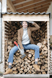 Portrait of smiling mature woman with axe sitting on firewood - VYF00011