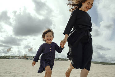 Portrait of happy little girl walking hand in hand with her mother on the beach, The Hague, Netherlands - OGF00163