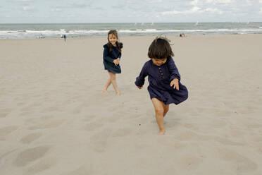 Two little girls playing on the beach, Scheveningen, Netherlands - OGF00166