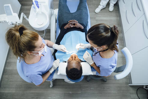 Female dentist and assistent attending patient in medical practice - JCMF00397