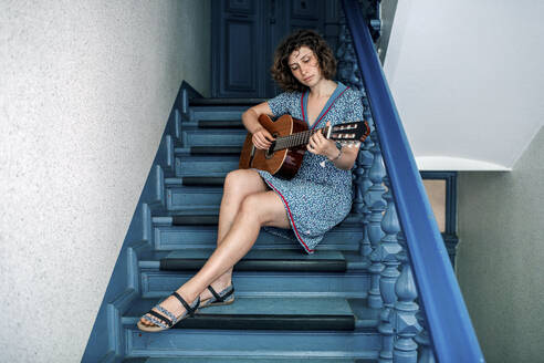 Portrait of young woman sitting on stairs playing guitar - OGF00192