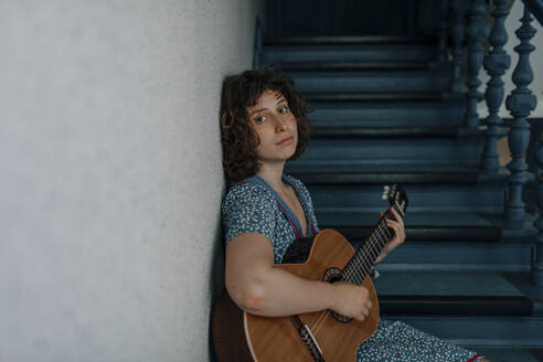 Portrait of young woman sitting on stairs playing guitar - OGF00195