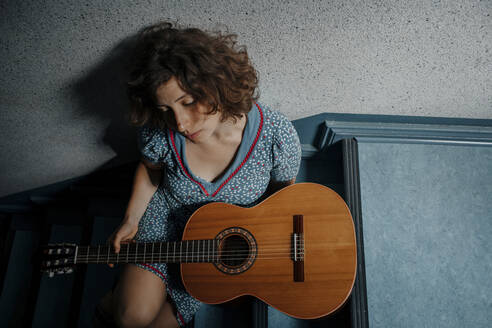 Sad young woman sitting on stairs with guitar - OGF00204