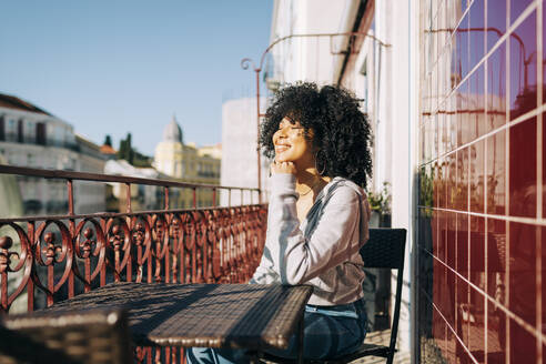 Happy young woman with curly hair sitting on balcony enjoying the sunshine - DCRF00080