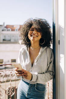Portrait of happy young woman with curly hair holding cell phone on balcony - DCRF00086