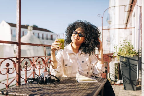 Smiling young woman with curly hair sitting at table on balcony with smoothie and camera - DCRF00104