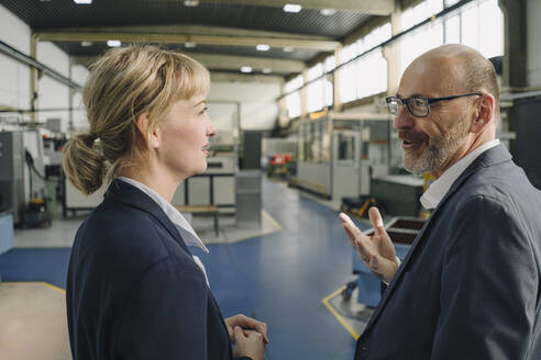 Businessman and businesswoman talking in a factory - KNSF07693