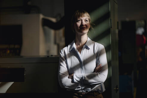 Portrait of a confident businesswoman leaning against a cabinet in a factory - KNSF07705