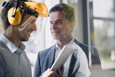Smiling businessman and man wearing safety helmet using tablet - KNSF07735