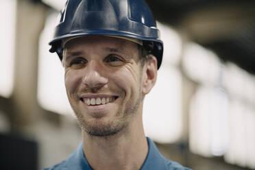 Portrait of a smiling worker in a factory wearing hard hat - KNSF07738