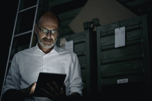 Businessman using tablet in a factory in the dark - KNSF07753