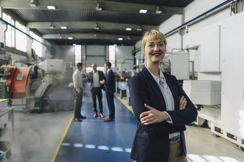 Portrait of a confident businesswoman in a factory with colleagues in backgound - KNSF07780