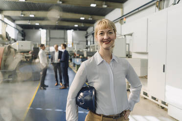 Portrait of a smiling woman with hard hat in a factory with colleagues in backgound - KNSF07783
