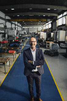 Portrait of a smiling businessman in a factory - KNSF07789