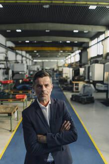 Portrait of a confident businessman in a factory - KNSF07795