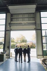 Rear view of business team standing at factory gate - KNSF07801