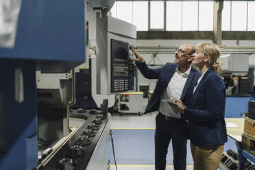 Businessman explaining machine to businesswoman in a factory - KNSF07813