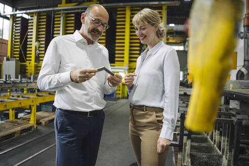 Man and woman examining workpiece in factory - KNSF07819