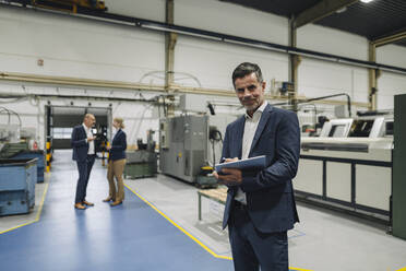 Portrait of a confident businessman using tablet in a factory with colleagues in background - KNSF07834