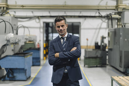Portrait of a confident businessman in a factory - KNSF07837
