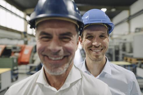 Portrait of two smiling men wearing hard hats in a factory - KNSF07843