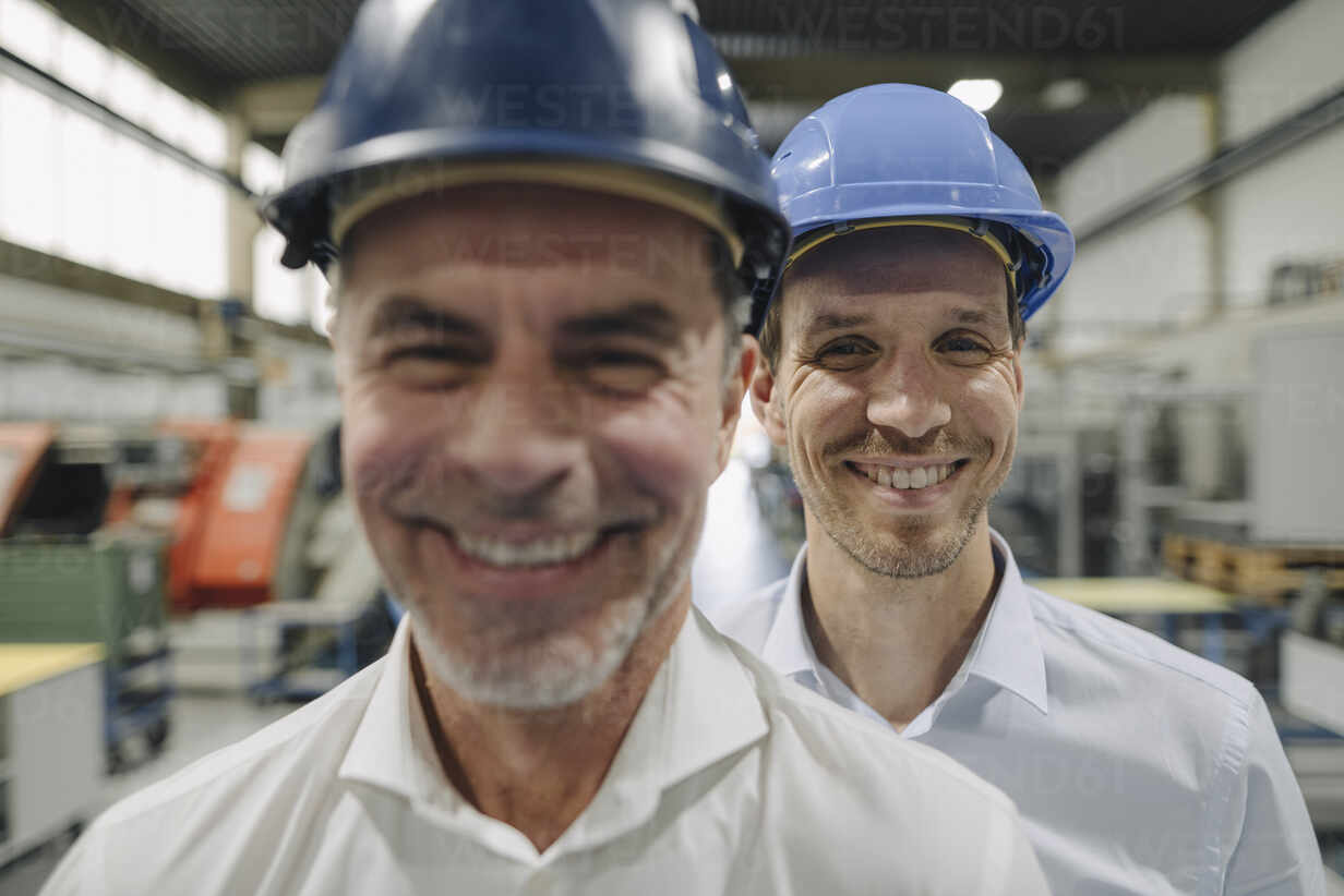 Portrait of two smiling men wearing hard hats in a factory - KNSF07843 - Kniel Synnatzschke/Westend61