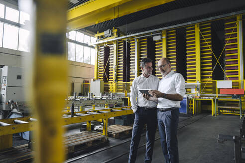 Two businessmen with tablet talking in a factory - KNSF07849