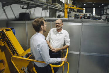 Two men talking in a factory - KNSF07864