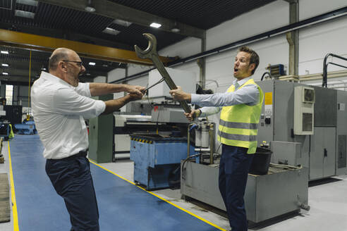 Businessman and man in reflective vest playfighting with large wrenches in a factory - KNSF07867