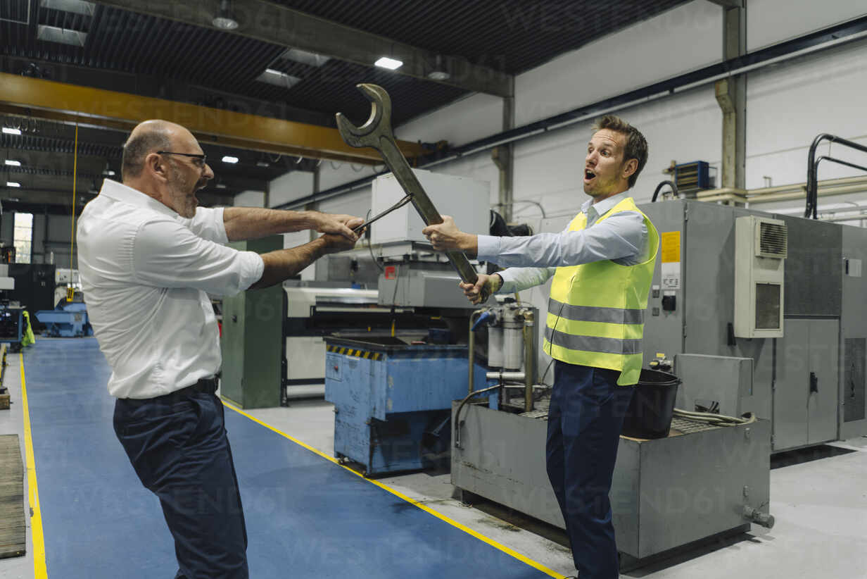 Businessman and man in reflective vest playfighting with large wrenches in a factory - KNSF07867 - Kniel Synnatzschke/Westend61