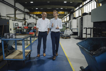Two men walking and talking in a factory - KNSF07873