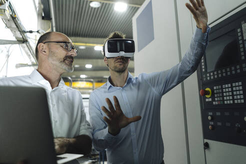 Two men with VR glasses in factory - KNSF07876
