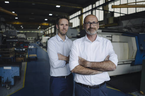 Portrait of two confident men in a factory - KNSF07882