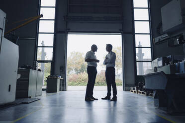 Two men talking at open gate in a factory - KNSF07885