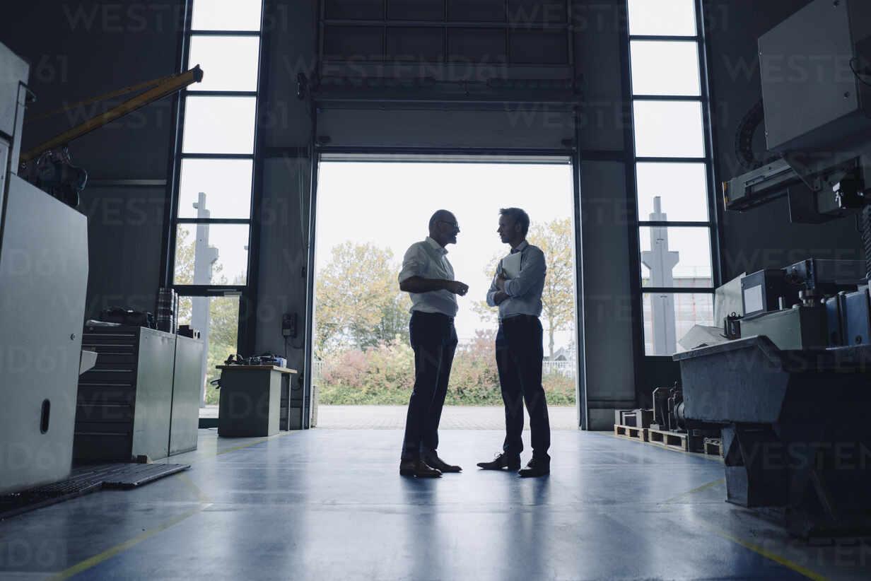 Two men talking at open gate in a factory - KNSF07885 - Kniel Synnatzschke/Westend61