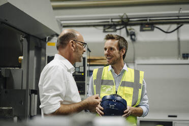 Businessman talking to smiling man in reflective vest in a factory - KNSF07888
