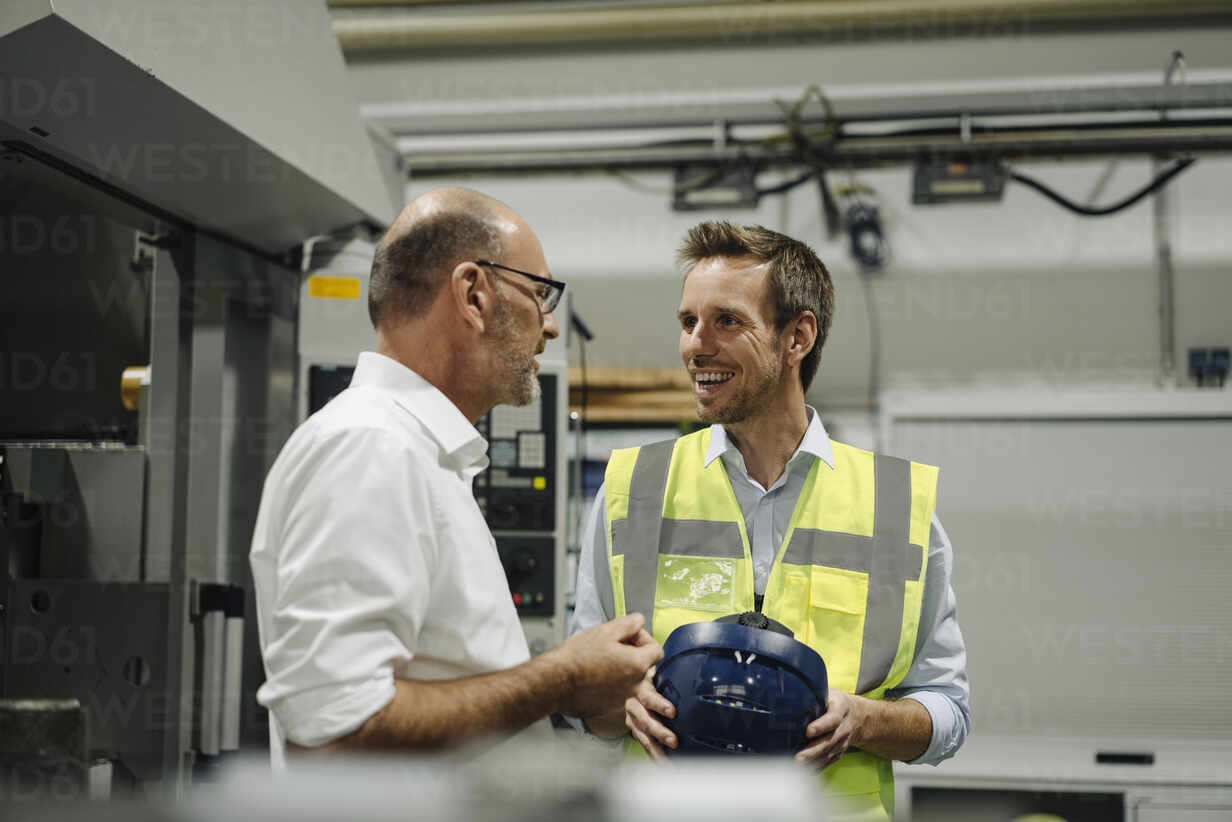 Businessman talking to smiling man in reflective vest in a factory - KNSF07888 - Kniel Synnatzschke/Westend61