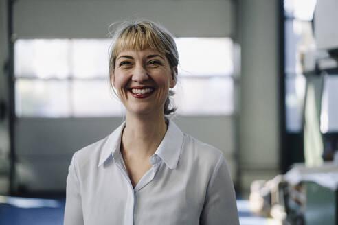 Portrait of a happy businesswoman in a factory - KNSF07894