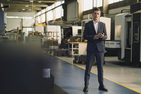 Portrait of a businessman with cell phone in a factory - KNSF07897