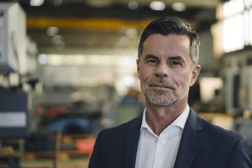 Portrait of a confident businessman in a factory - KNSF07900