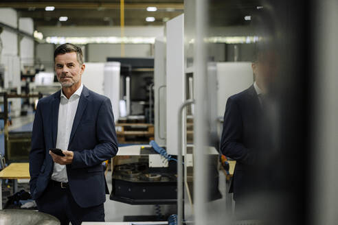 Portrait of a confident businessman in a factory - KNSF07909