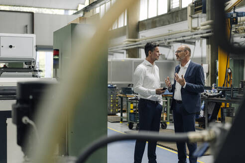 Two businessmen talking in a factory - KNSF07915