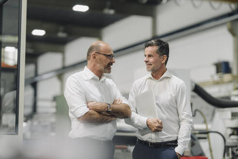 Two businessmen talking in a factory - KNSF07918
