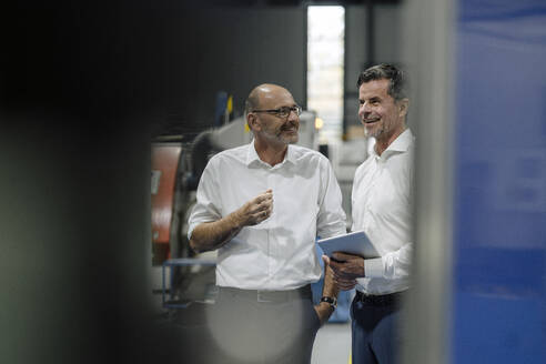 Two smiling businessmen talking in a factory - KNSF07921