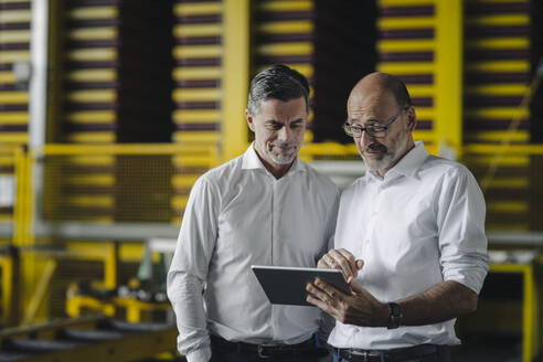 Two businessmen using tablet in a factory - KNSF07924