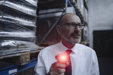 Man with glowing scanner in factory warehouse - KNSF07927