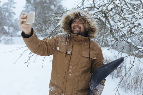 Portrait of smiling man with snow shovel taking selfie with cell phone - KNTF04427