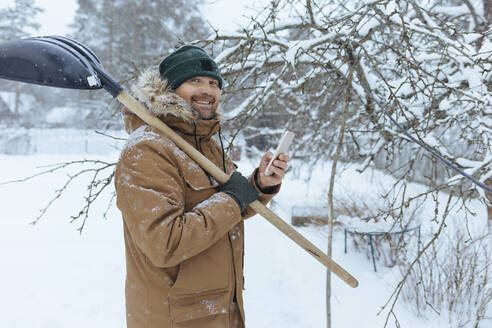 Portrait of smiling man with snow shovel and cell phone - KNTF04430