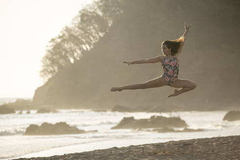 Teenage girl practicing gymnastic at seafront by sunset, Jaco Beach, Costa Rica - AMUF00013